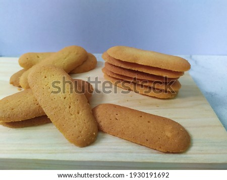 Selective focus of Lidah kucing are cookies shaped like a long and thin cat's tongue. In Indonesia, lidah kucing is the popular kue kering or cookie. Look like noised with white background and cookies Stock fotó ©