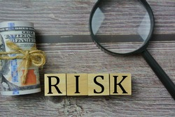 Selective focus of magnify glasses, and wooden cube with word RISK. Risk management, investment, buying, and selling concept.