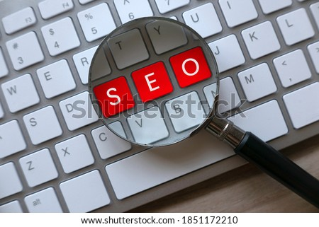 Selective focus of magnifying glass and computer keyboard with red key written with SEO Search Engine Optimization on a wooden background. Stock photo ©