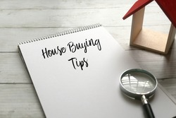 Selective focus of magnifying glass,wooden house and notebook written with House Buying Tips on wooden background.