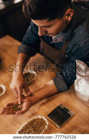 selective focus of man checking coffee beans quality at wooden table #777762526