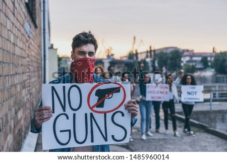 selective focus of man with scarf on face holding placard with no guns lettering near multicultural people  #1485960014