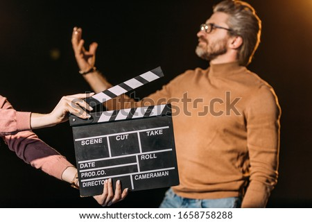 selective focus of mature actor performing role with clapboard in front Foto stock ©