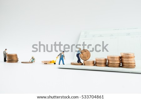 Selective focus of miniature and stack of coins with account book finance and banking concept for background.concept in grow and walk step by step for success in business