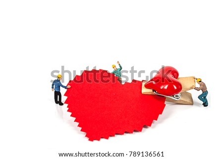 selective focus of miniature workers holding red heart shape wood clip isolated on white background , abstract background to valentine concept. #789136561