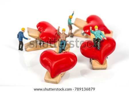 selective focus of miniature workers holding red heart shape wood clip isolated on white background , abstract background to valentine concept. #789136879