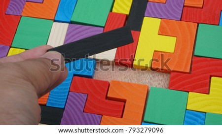 Selective focus of multicolored wooden jigsaw bricks relating to problem solving at early stage of education #793279096