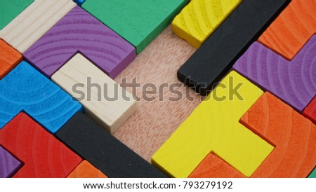 Selective focus of multicolored wooden jigsaw bricks relating to problem solving at early stage of education #793279192