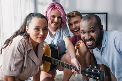 Selective focus of multicultural business people with acoustic guitar looking at camera in office