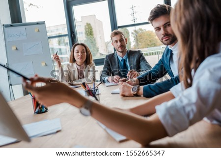 selective focus of multicultural businesspeople looking at coworker in office