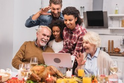Selective focus of multicultural family having video call on laptop near food during thanksgiving