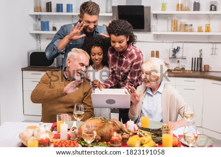 Selective focus of multiethnic family having video call on laptop during thanksgiving