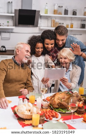 Selective focus of multiethnic family having video chat on digital tablet near turkey during thanksgiving