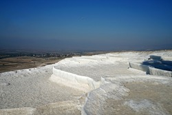 Selective focus of Natural landscape at Pamukkale (Cotton castle) mineral-rich thermal waters flowing down white travertine terraces on a nearby hillside formed by ancient hot springs- Denizli, Turkey