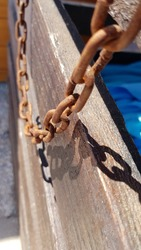 Selective focus of old rusty metal chain links on defocused wooden background in bright sunlight with dark shadows. Vintage protection chains damaged by corrosion