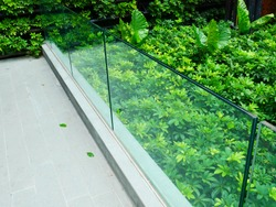 selective focus of outdoor frameless glass railing. SGP or PVB film laminated glass partition.