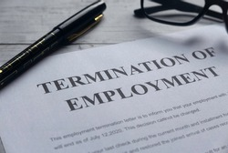 Selective focus of pen,glasses and Termination of Employee letter on a white wooden background.