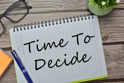 Selective focus of pen, spectacle, flower and notebook written with TIME TO DECIDE. Time management, decision time, leader and investment concept.
