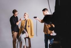 selective focus of photographer shooting how Makeup Artist doing makeup to stylish model
