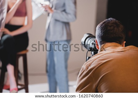 selective focus of photographer taking photo of model and hairstylist