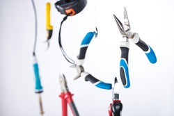 Selective focus of pliers and tools levitating in air isolated on grey
