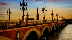 Selective focus of  Pont de Pierre bridge and motion blur of tram in Bordeaux at sunset as the night sky scene