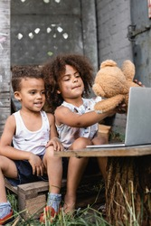 selective focus of poor african american kid holding dirty teddy bear near laptop outside