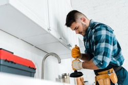 selective focus of repairman holding plunger in kitchen