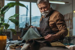 selective focus of senior cobbler holding pieces of genuine leather in workshop