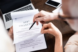 Selective focus of senior man holding pen near wife with debt collection lettering on papers