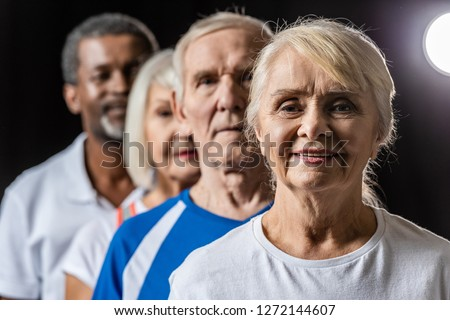 selective focus of senior woman and her friends looking at camera on black with spotlight