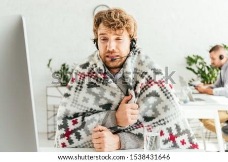 selective focus of sick bearded broker wrapped in blanket near coworker in office