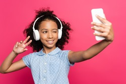 selective focus of smiling curly african american kid in headphones showing victory sign while taking selfie on smartphone isolated on pink