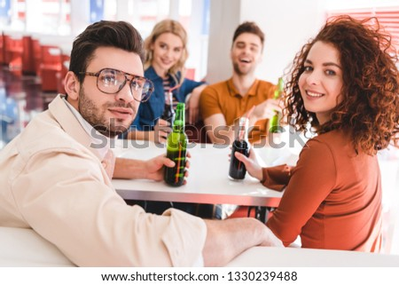 selective focus of smiling friends holding glass bottles with soda and beer and looking at camera