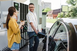 Selective focus of smiling man looking at wife with coffee to go while refueling car on gas station
