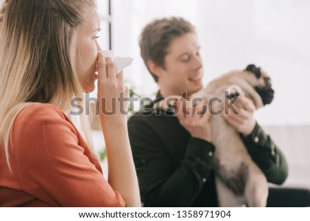 selective focus of sneezing woman allergic to dog looking at happy man with pug