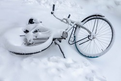 Selective focus of snow covered bicycle fall on the ground, Heavy and snowy day in winter with white fluffy snowflakes, Cycling is a common mode of transport in Holland, Amsterdam, Netherlands.
