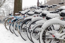 Selective focus of snow covered bicycle parked on the parking rack, Heavy and snowy day in winter with white fluffy snowflakes, Cycling is a common mode of transport in Holland, Amsterdam, Netherlands