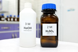 Selective focus of sodium hydroxide base and sulfuric acid solution in brown glass and plastic bottle inside a chemistry laboratory. White background with copy space.