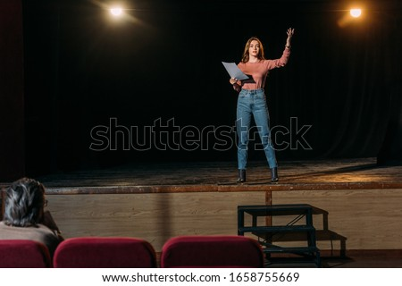 selective focus of stage director and actress reading scenario in theater