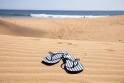 selective focus of striped flip flops on sand hills near Atlantic ocean against clear blue sky in Maspalomas, Gran Canaria