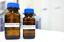 Selective focus of strong Hydrochloric acid solution in brown amber bottle. Blur laboratory backdrop with copy space.