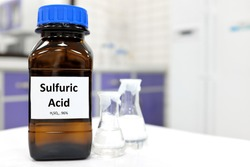 Selective focus of strong sulfuric acid chemical in brown amber glass bottle inside a laboratory with copy space.