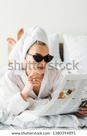selective focus of stylish barefoot woman in shirt, sunglasses, jewelry and with towel on head reading newspaper in bed