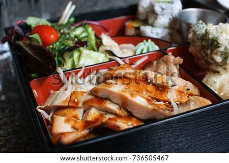 selective focus of teriyaki glazed chicken in a bento box