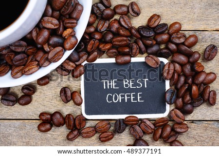 Selective focus of THE BEST COFFEE text written on the chalkboard, coffee beans and white cup on the wooden background.