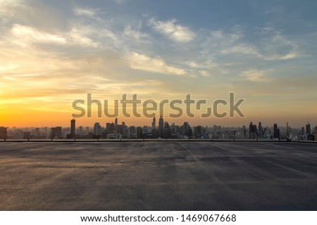 Selective focus of the cement floor with cityscape background in the evening at Bangkok , Thailand. Cement floor on the roof with sunset over the building in capital.