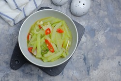 Selective focus of Tumis Labu siam - Indonesian Spicy stir fry chayote, typical Indonesian daily homedish, served in grey bowl over rustic grey background. Top view of Squash stir fry
