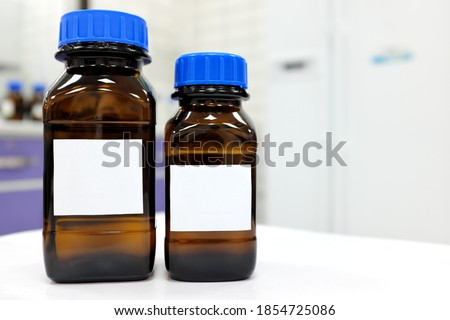 Selective focus of two dark glass reagent bottle with unknown clear liquid chemical inside and blank label in a chemistry laboratory.