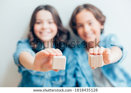 Selective focus of two wooden bricks in hands of contented boy and girl in blue clothes Stockfoto ©